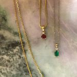 Emerald and diamond pendant and Ruby and diamond pendant with chains on a jadeite slab